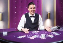 Jednou z méně známých dovedností blackjackových hráčů je schopnost číst z řeči těla dealera a využít to ve svůj prospěch. Může to znít divně, protože blackjack není jako poker, kde se podle chování protihráče snažíte posoudit sílu jeho karet, ale je to míněno vážně. V blackjacku se na základě chování dealera můžete dopracovat k tomu, jak si váš celkový součet vede v porovnání se základní kartou dealera. Jinými slovy řečeno, schopnost číst z chování jako jsou gesta a narážky vás může dovést k tomu, jakou kartu dealer má. Teď, když už jsme vám prozradili základní koncept, můžeme se podívat na konkrétní tipy. Co vám řekne základní chování dealera? Někteří lidé tvrdí, že ať už nám dealer chováním něco prozradí či nikoliv, stejně nám to nic neřekne. Zkušení blackjackový hráči se ovšem schodují, že z chování dealerů lze číst. Samozřejmě, stejně jako samotní blackjackový hráči, i někteří dealeři jsou horší než ostatní, což znamená, že máte větší pravděpodobnost na čtení informací. To znamená, že jednou z největších dovedností při hře blackjacku je nalezení čitelného dealera. Příklady toho, co vám chování dealera řekne Myšlenka čtení z chování dealera nepracuje s tím, abyste určili přesnou hodnotu karty, jako spíš s tím, abyste určili rozsah možných karet. Na následujících řádcích najdete nejčastější chování dealerů v případě, že drží určitou skupinu karet: Chování dealerů v případě, že drží low kartu – karty 2, 3, 4, 5 a 6 se při běžném ohnutí špatně čtou, takže je dealeři musejí odkrýt (a ohnout) ještě víc než je obvyklé u zbytku karet. Aby se ujistili, že nemají eso, někdy karty kontrolují třeba i dvakrát. K záměně dochází zejména v případě karty s hodnotou 4, protože se esu podobá nejvíc. Chování dealerů v případě, že drží vyšší kartu nebo kartu s obrázkem – vysoké karty s obrázkem a ty, které mají hodnotu 7, 8, 9 a 10 jsou při běžném ohnutí lépe viditelné, takže dealer je nepotřebuje zase tolik zkoumat. Pokud se tedy dealer na kartu podívá velmi rychle, můžete si být v